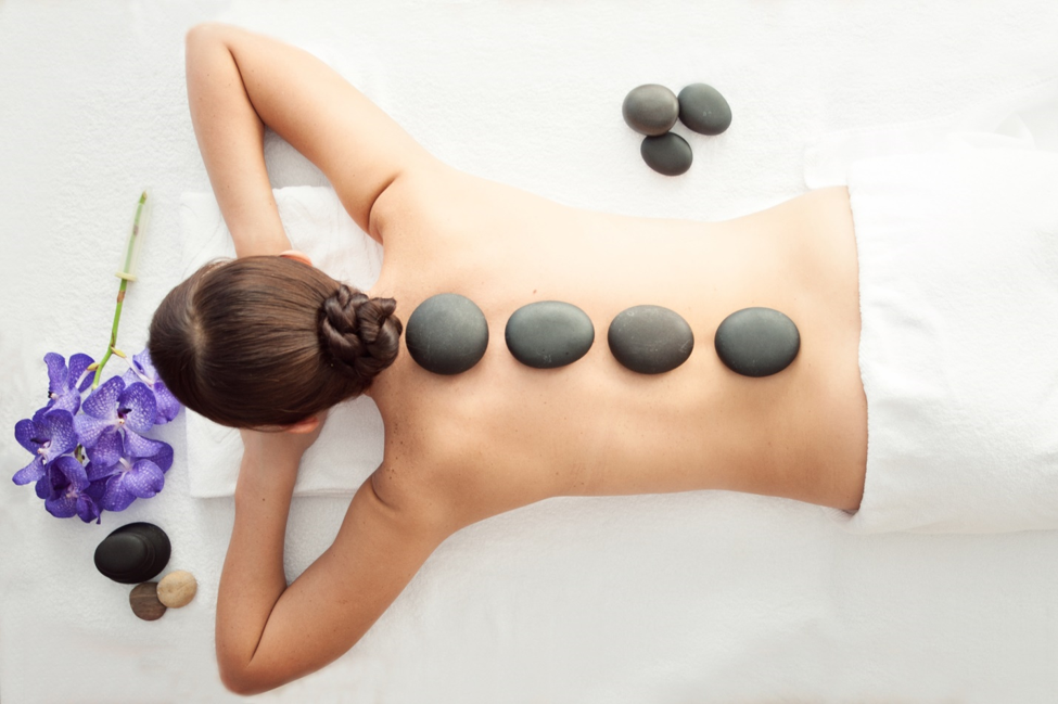 Woman Laying Down and Has Hot Stones on Her Back
